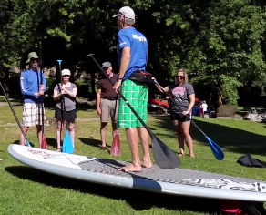 Instructor demonstrating paddling a stand up paddleboard