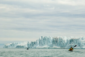 Jaime Sharp paddle svalbard with ice cliffs and glaciers behind him