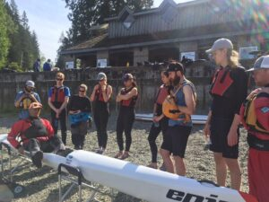 Kenny teaching surfski on the beach in Deep Cove