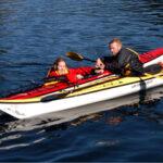instructor helping kayaker remount her boat