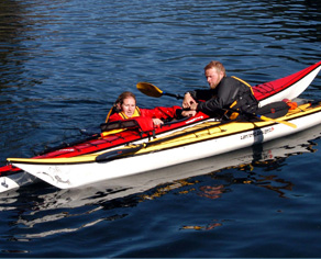 instructor helping kayaker remount her boat