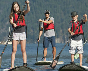 kids and adults stand up paddling in deep cove